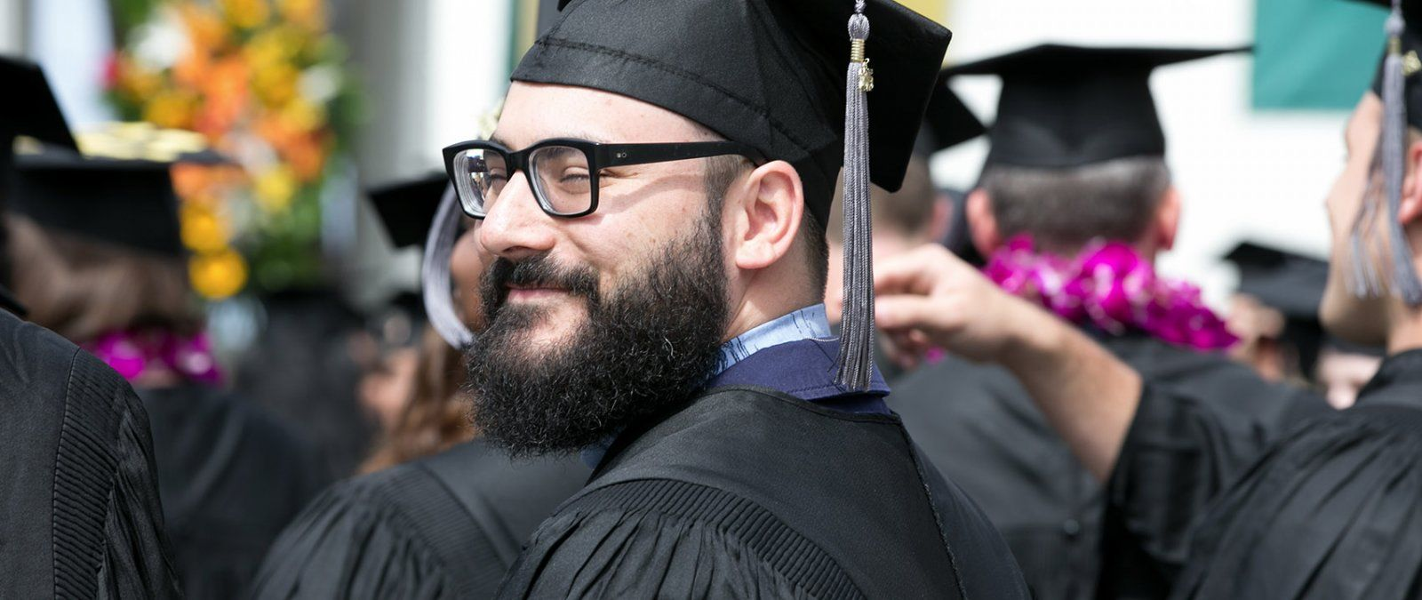 A PLNU graduate student smiles as he stands for graduation