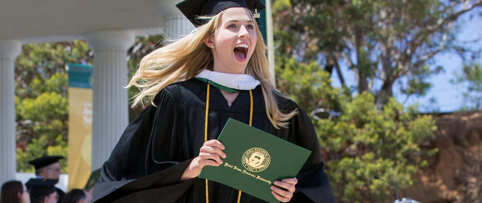 A female PLNU student excitedly smiles to the crowd after receiving her diploma.