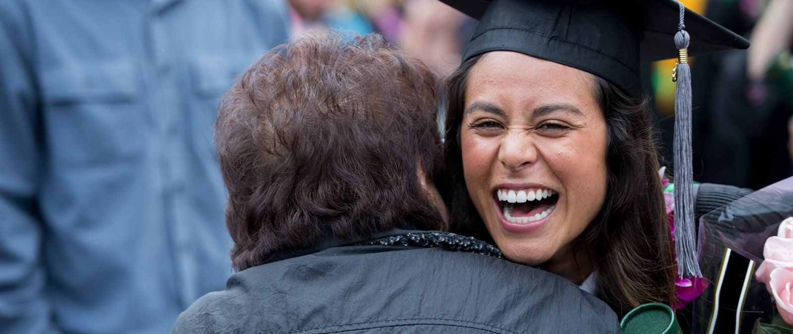 A PLNU graduate student is embraced by a grandparent after commencement.