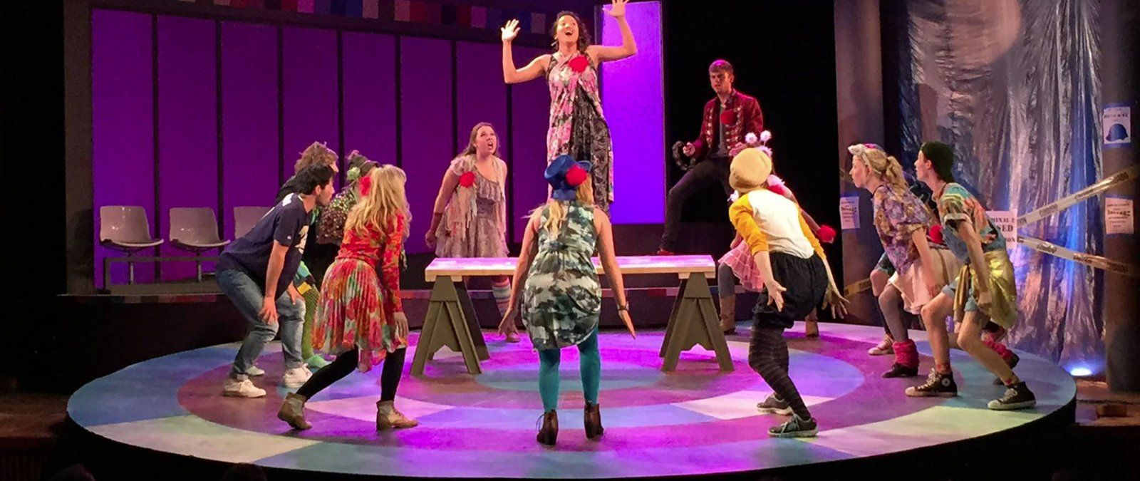 A group of student actors in colorful costumes circle around at a singer on a elevated platform during the performance of Godspell