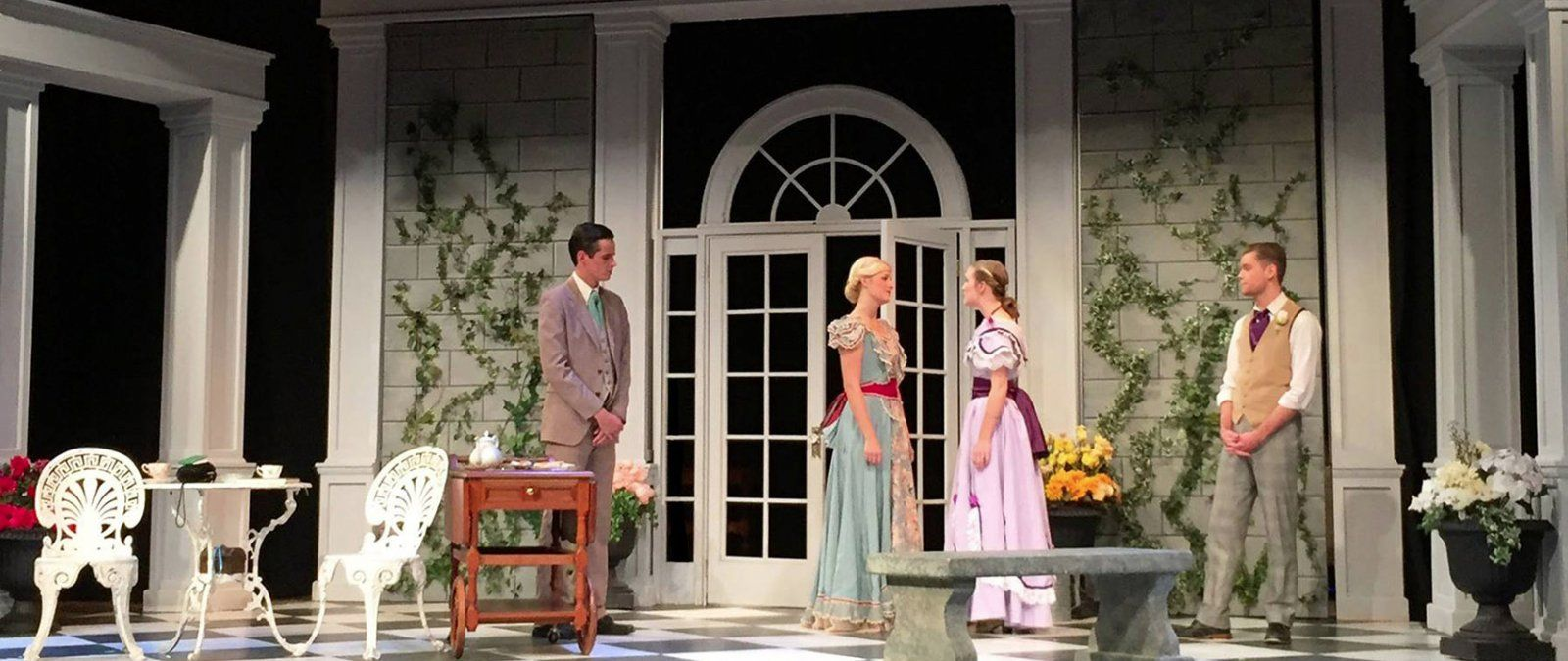 Two men and two women gently conversing on the stage of The Importance of Being Ernest