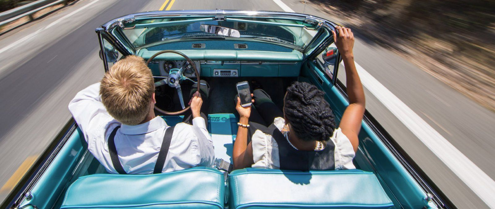 Two students in an old convertible driving fast