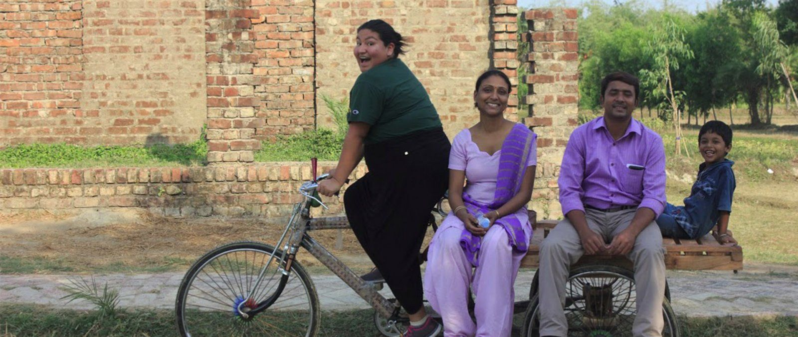 A student pedals a bike carrying a family in India.