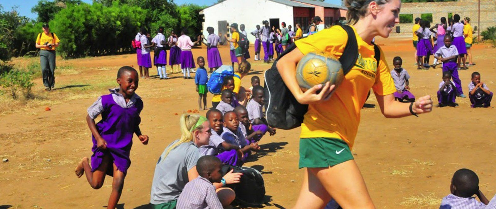 A female soccer player carrying a soccer ball is chased by a child in Zambia around a circle.