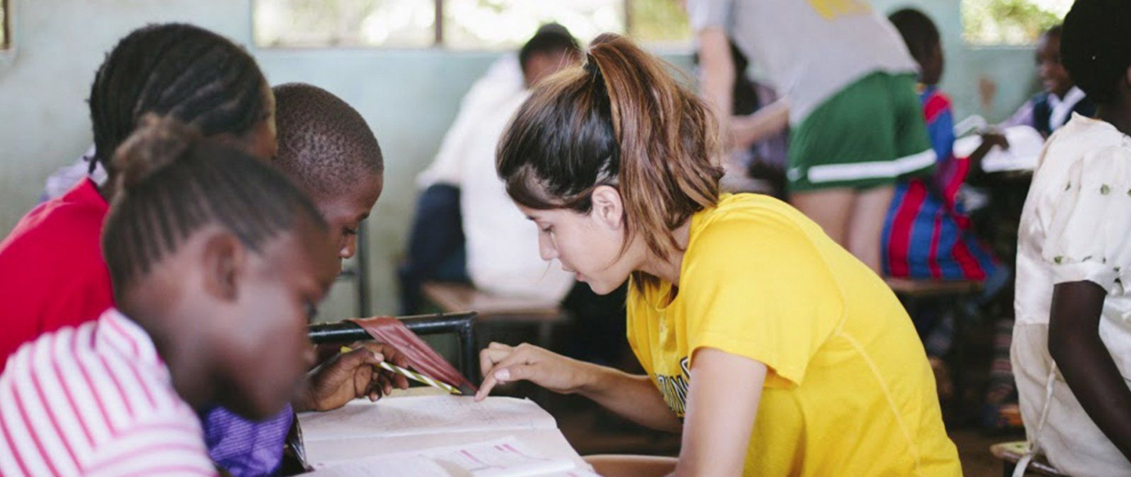 A PLNU student works with a student on homework while on a Loveworks trip to Zambia