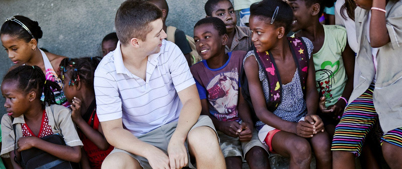 A PLNU student interacts with a group of children on a Loveworks trip in Madagascar.