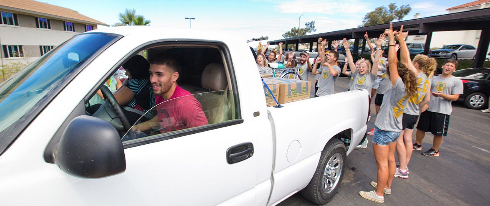 Current PLNU students eagerly help new freshmen unload their car.