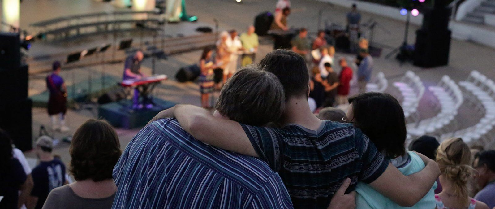 A family worships together in the Greek Amphitheatre during NSO.