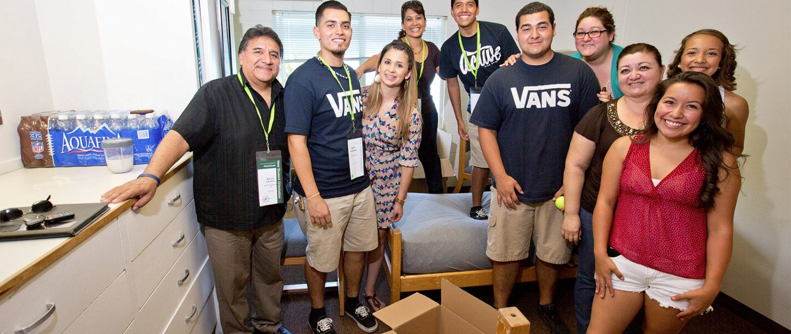 A group of new students and their parents pose for a photo in a residence hall.