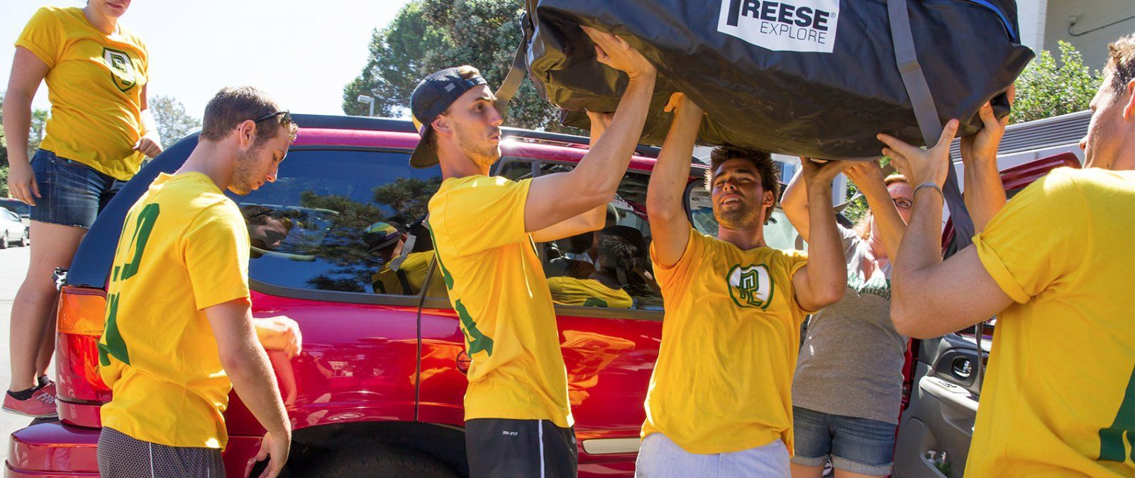 PLNU student leaders help a new student unload her car.