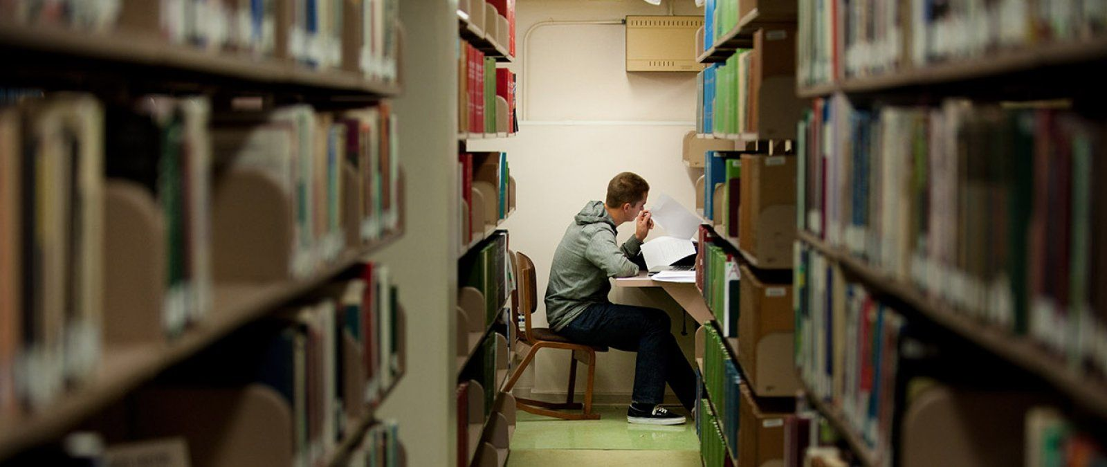 A male student sits studying at a long row of library stacks