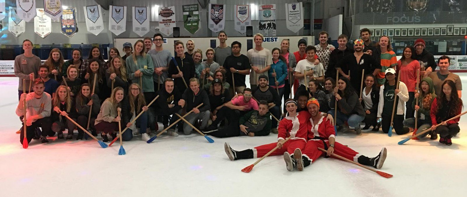 A large group of PLNU transfer students play broomball at a TAG event