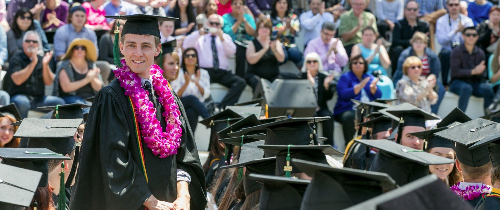 Jordan Thompson stands up to receive his diploma at PLNU's commencement ceremony