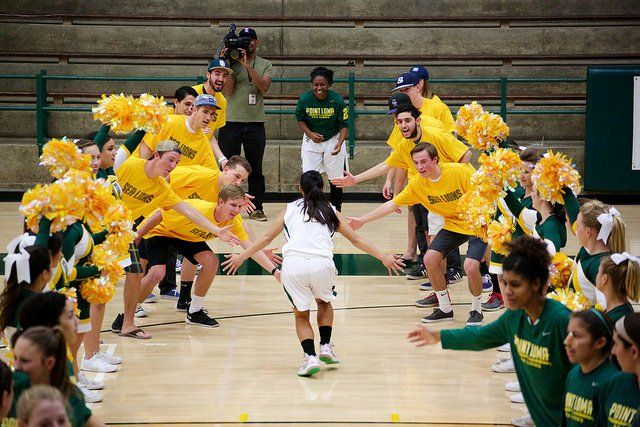 A women's basketball player runs through a tunnel of fans