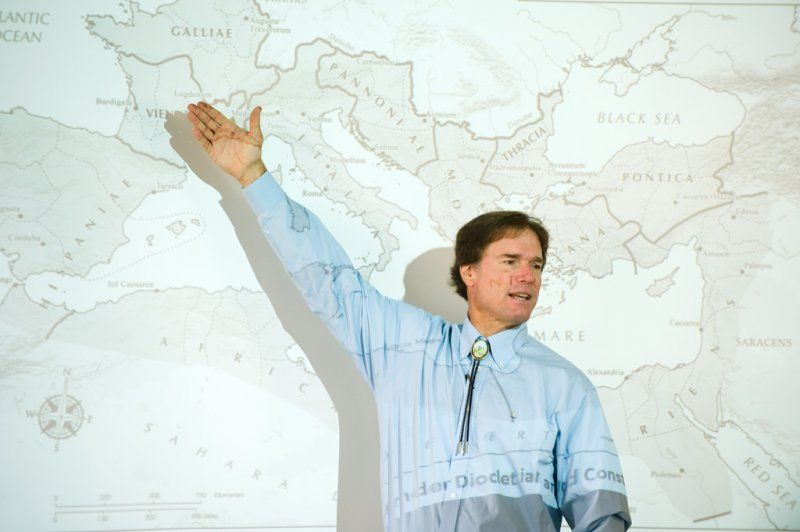 Dr. Kennedy teaching in front of a world map